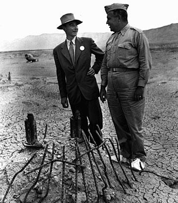 Photo depicting Dr. Oppenheimer and General Groves examining the remains of one the steel test tower bases at the Trinity test site